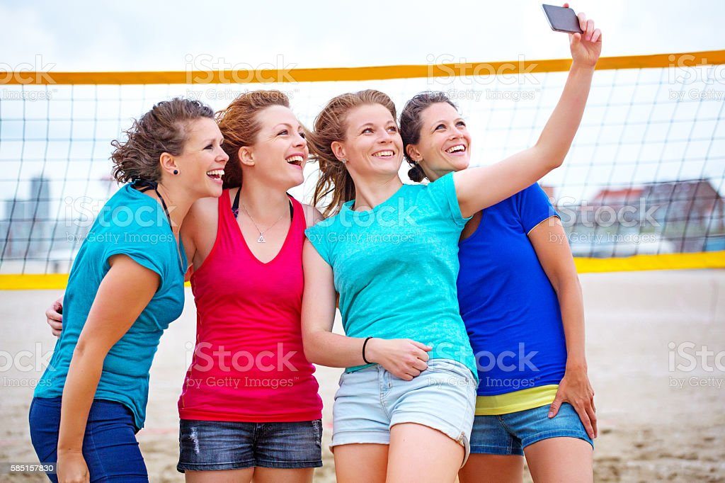 Four beautiful female friends taking a selfie on summer beach stock photo