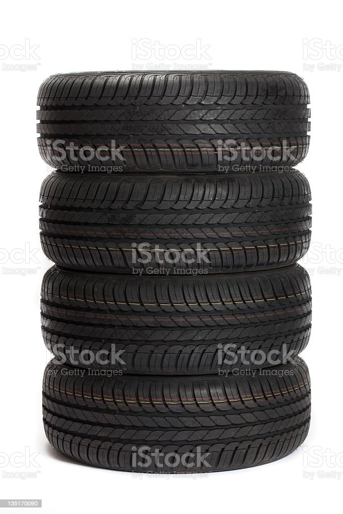 Four black car tires stacked on top of one another stock photo