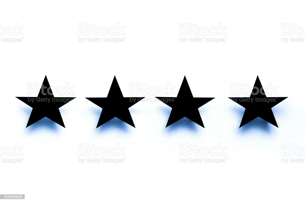 Four black stars against with shadows, white background, copy space stock photo