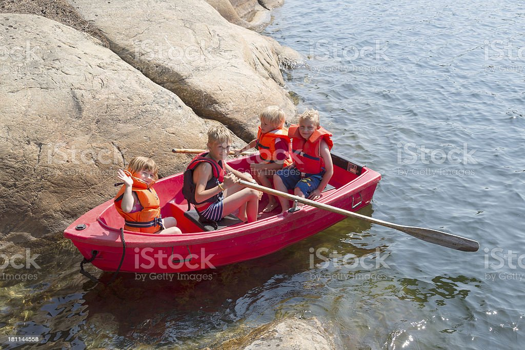 Four blond children with life jackets in red rowing boat. royalty-free stock photo