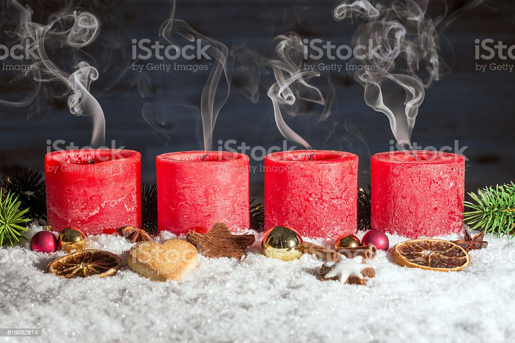 Four blown out advent candles in snow stock photo