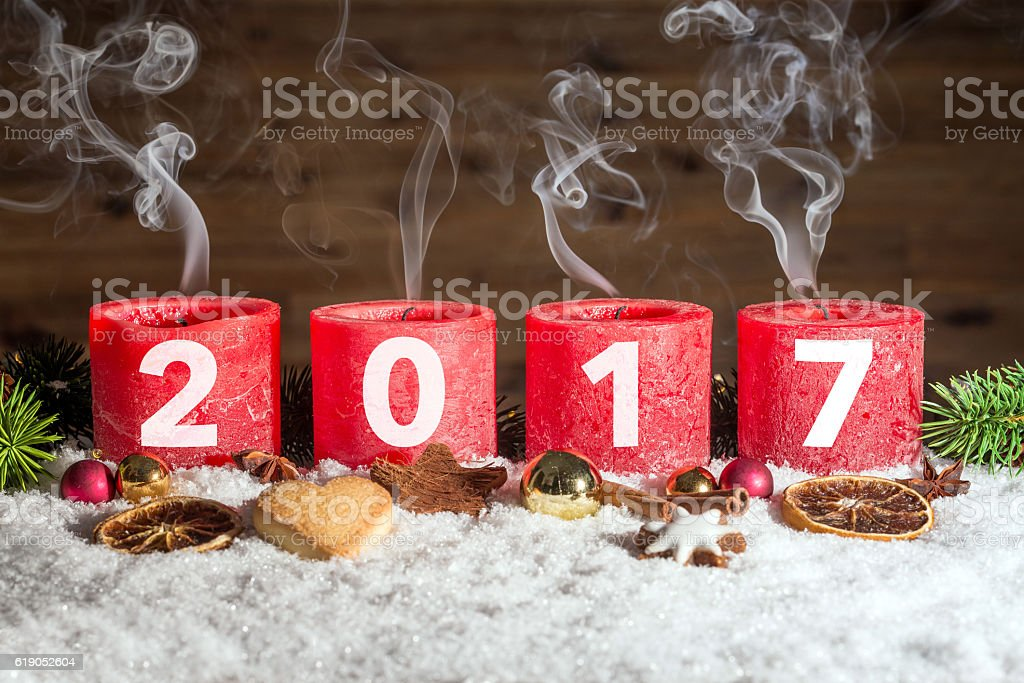 Four blown out advent candles with 2017 in snow stock photo