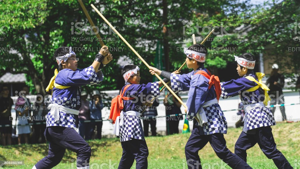 Four boys playing kendo in a field stock photo
