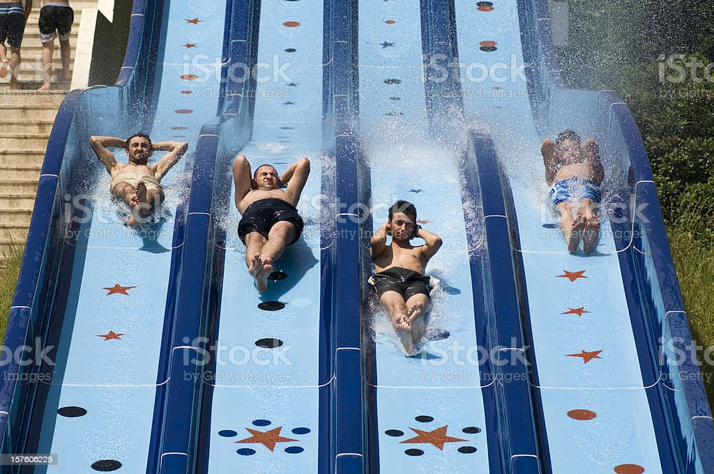 Four boys racing down the water slide royalty-free stock photo