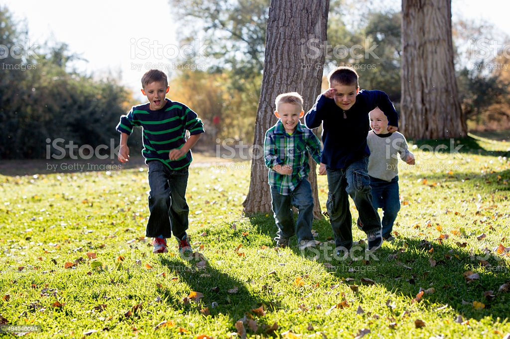 Four Brothers Running in a park in the Autumn stock photo