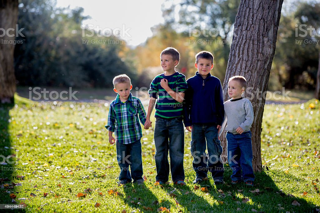 Four Brothers Walking Together in the Park stock photo