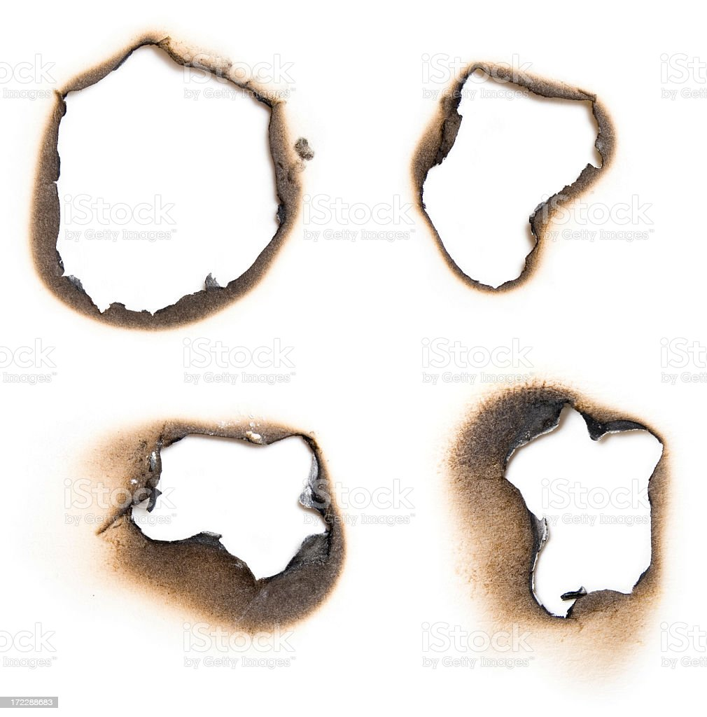 Four burn holes on a paper in white stock photo