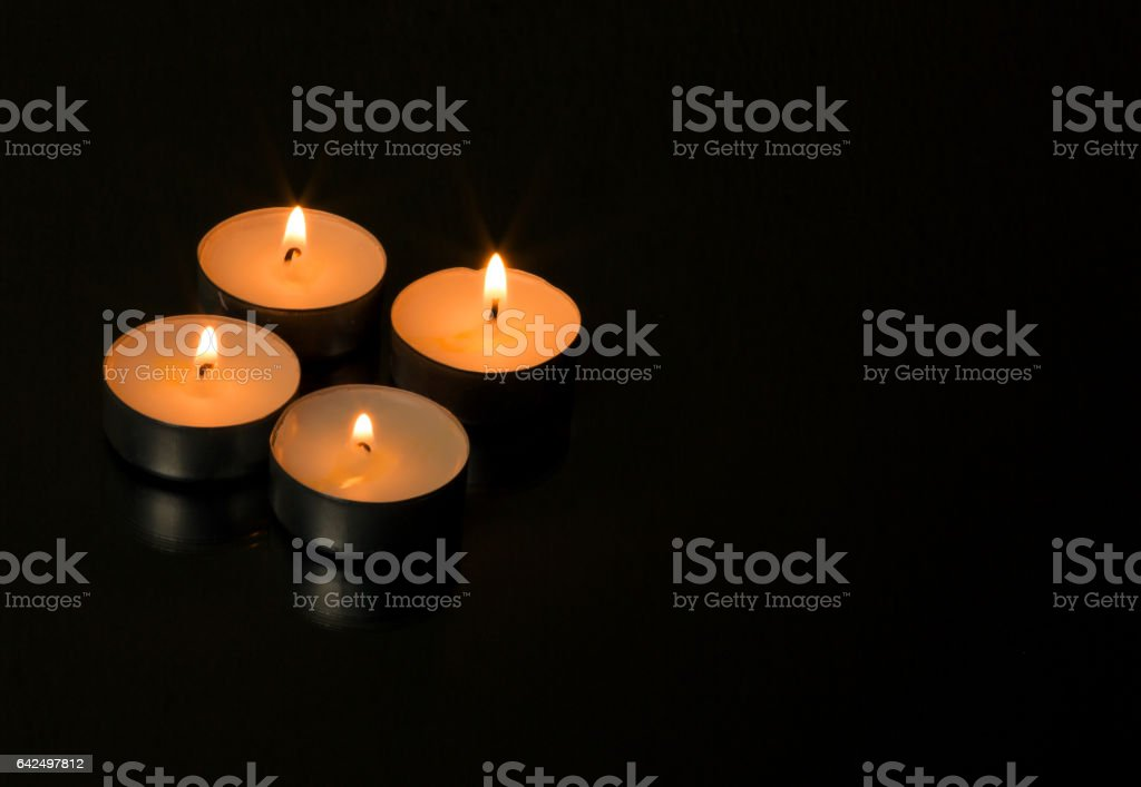 Four burning candles with reflection stock photo