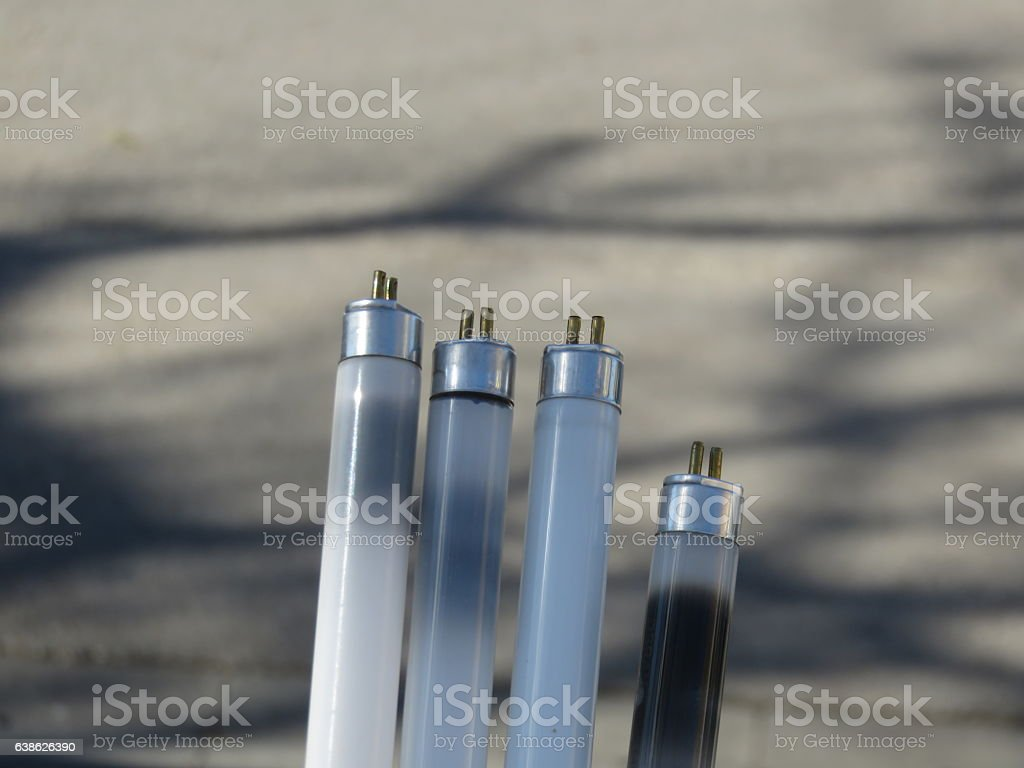 Four burnt fluorescent lamps stock photo