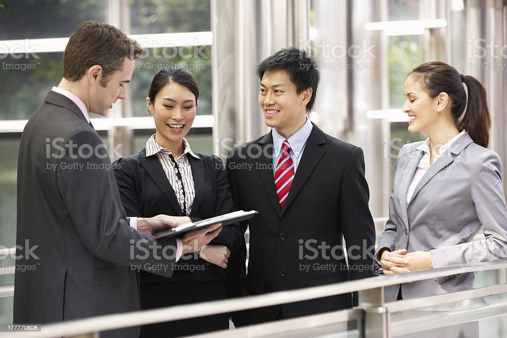 Four Business Colleagues Discussing Document Outside Office stock photo