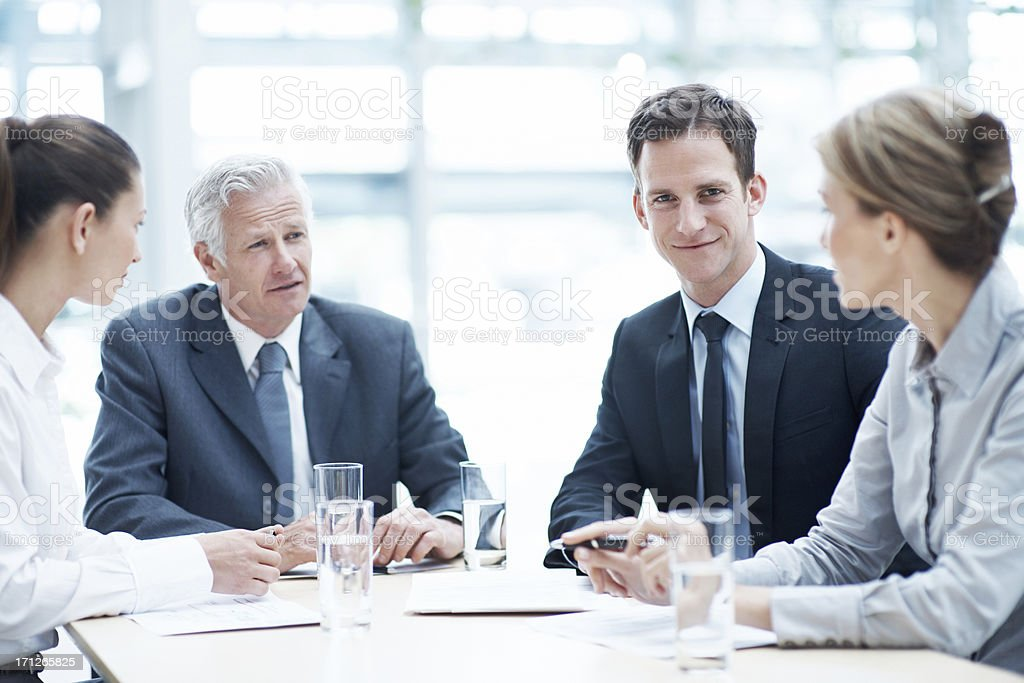 Four business executives conversing at table stock photo