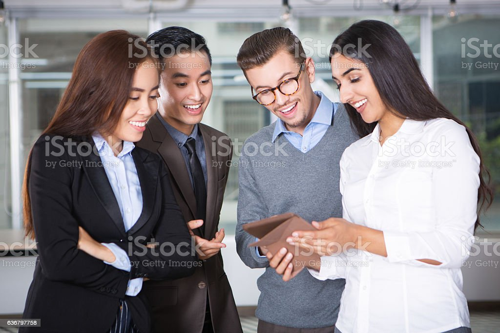 Four Business People Looking at Tablet Screen stock photo