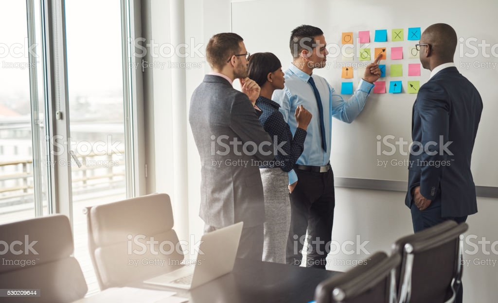 Four business people planning with sticky notes stock photo