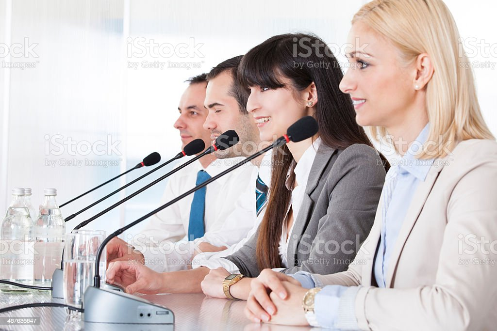 Four Business People Speaking In Microphone in business suit stock photo