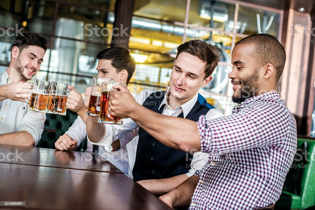 Four businessmen friends drink beer and spend time together stock photo
