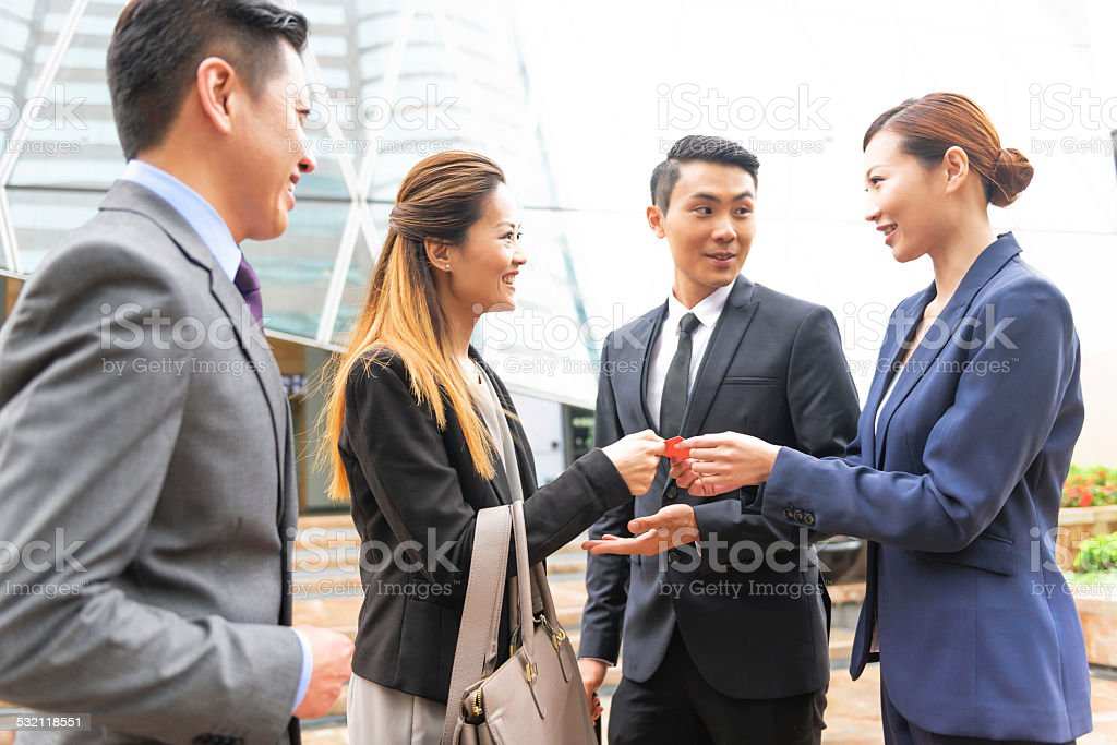 Four Businessmen with Business Cards, Hong Kong, China, Asia stock photo