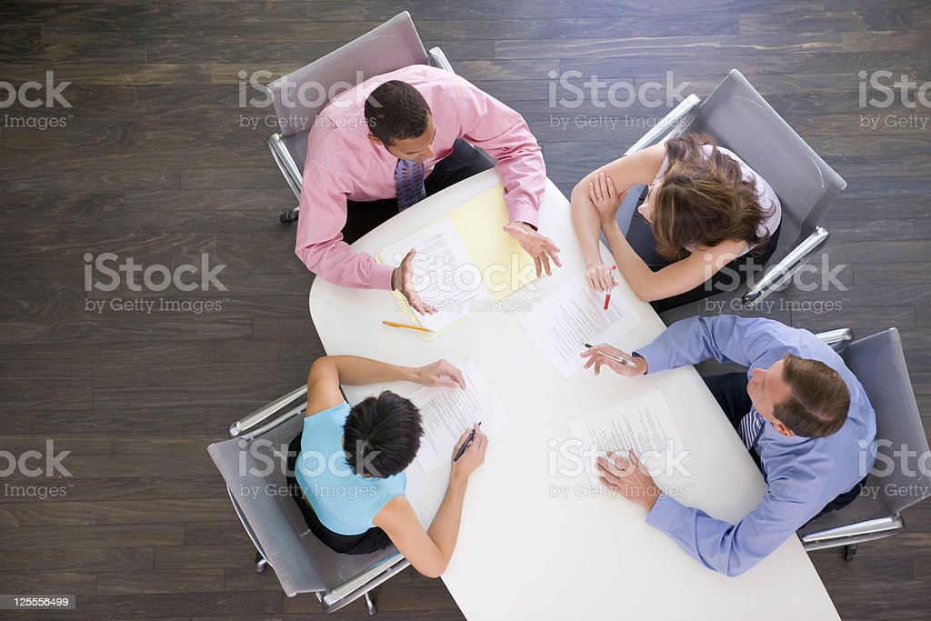 Four businesspeople at boardroom table stock photo