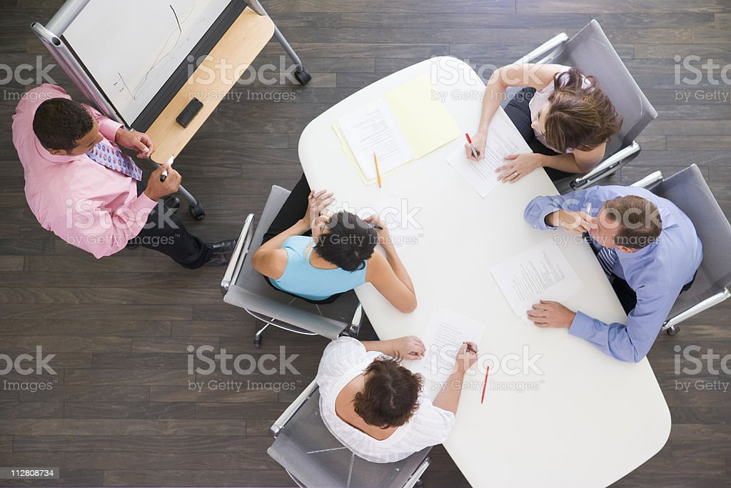 Four businesspeople at boardroom table watching presentation royalty-free stock photo