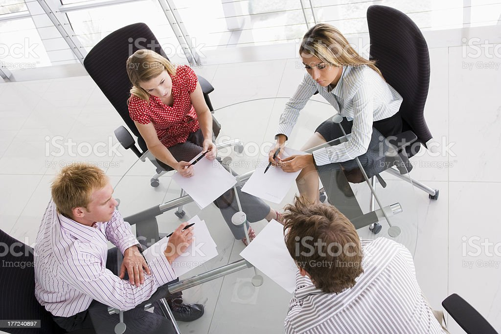 Four businesspeople in a boardroom with paperwork royalty-free stock photo