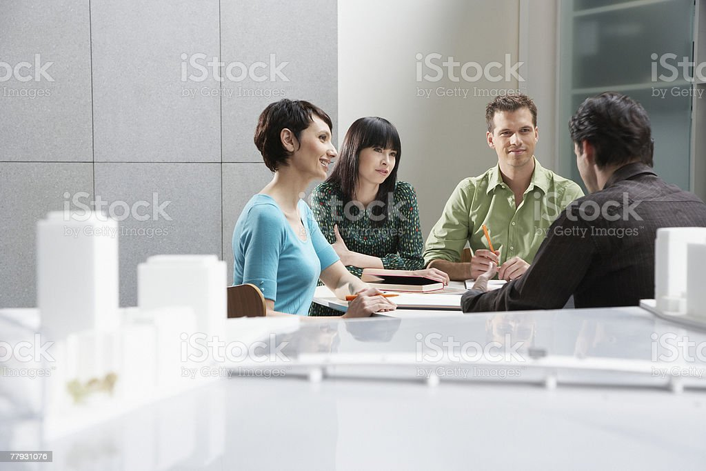 Four businesspeople in an office by a city model royalty-free stock photo