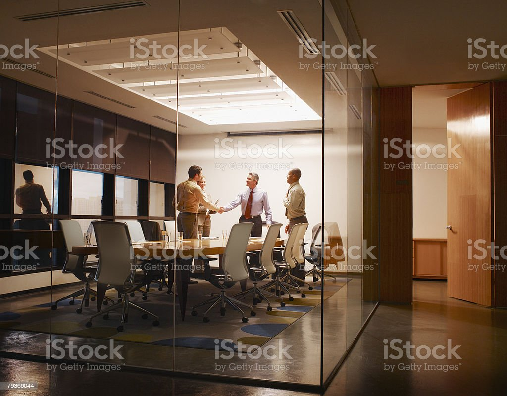 Four businesspeople in boardroom with two shaking hands stock photo