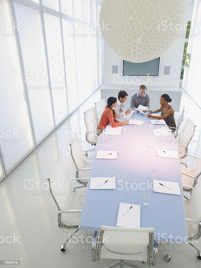 Four businesspeople in boardroom working royalty-free stock photo