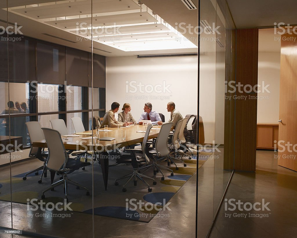 Four businesspeople in boardroom working stock photo