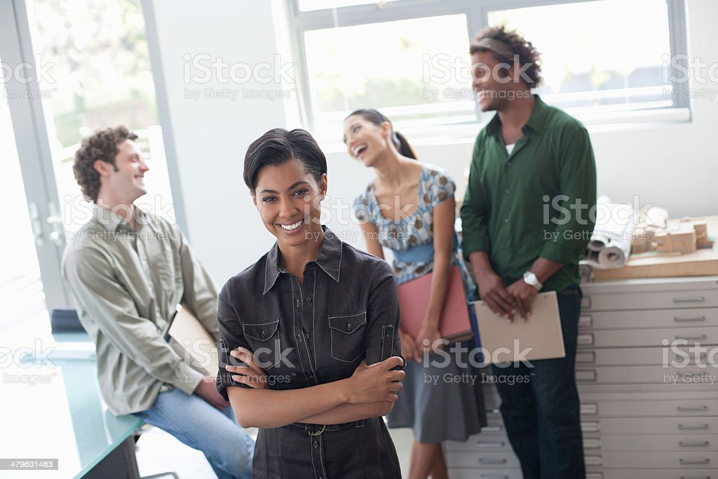 Four businesspeople in office smiling stock photo