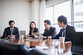 Four businesspeople meeting in a conference room.