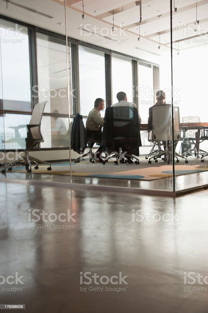 Four businesspeople sitting at a boardroom table royalty-free stock photo