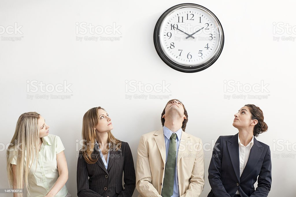 Four Businesspeople Watching Clock stock photo
