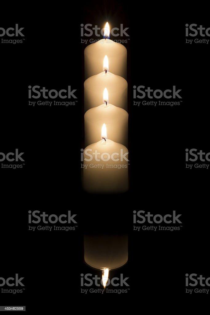 Quattro candele riflettono su sfondo scuro foto stock royalty-free
