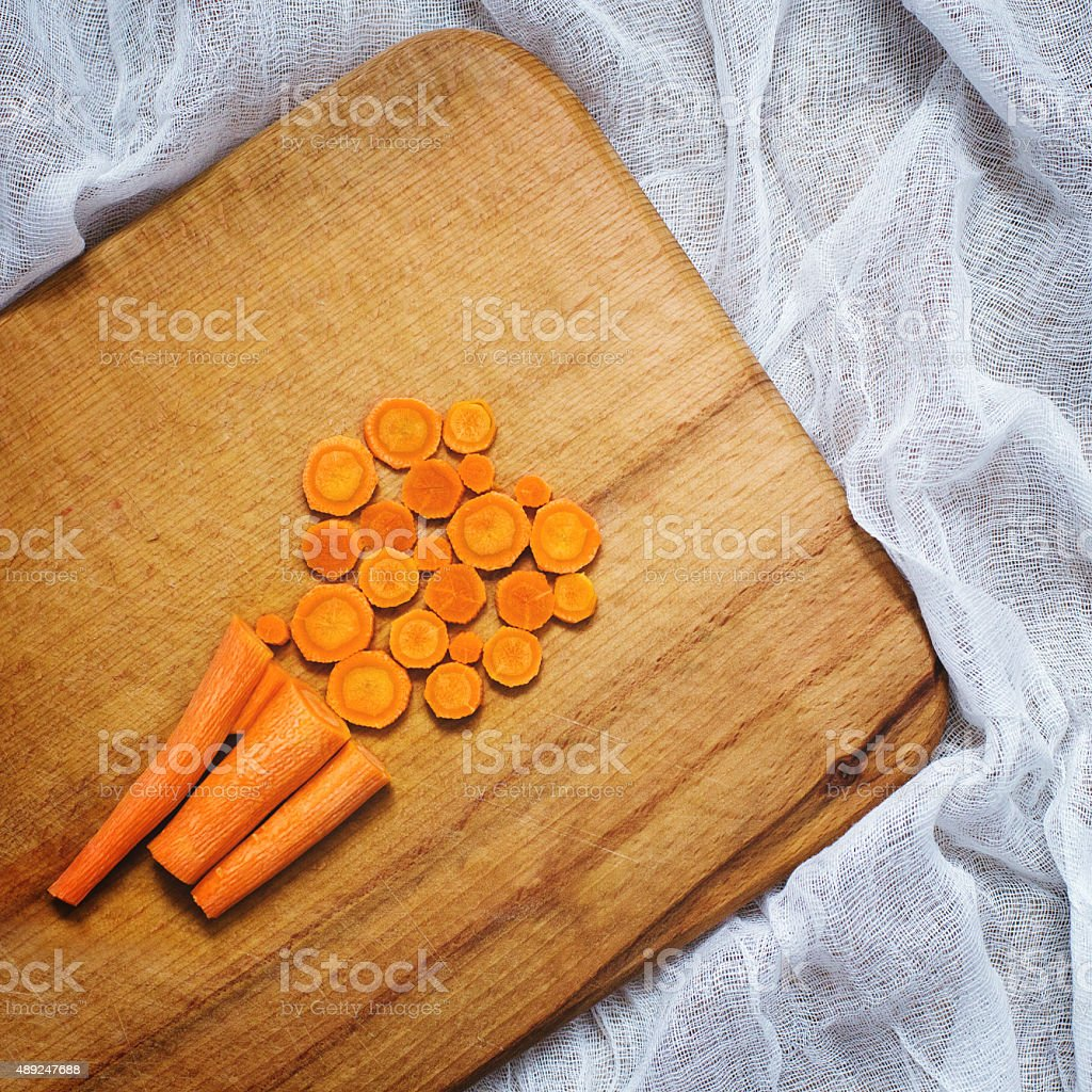 Four carrots on a wooden board and slices stock photo