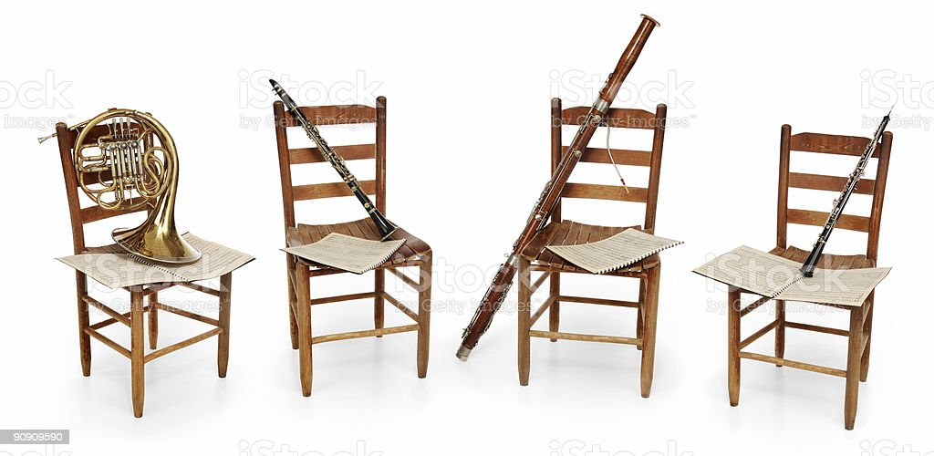 Four chairs with sheet music and musical instruments stock photo