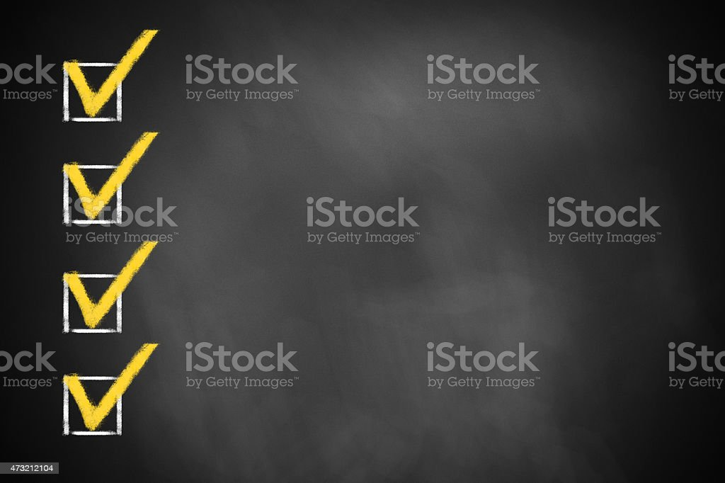 four checked checkboxes on chalkboard stock photo