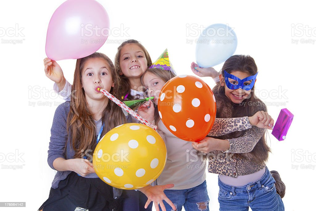Four children celebrating a birthday party with balloons stock photo