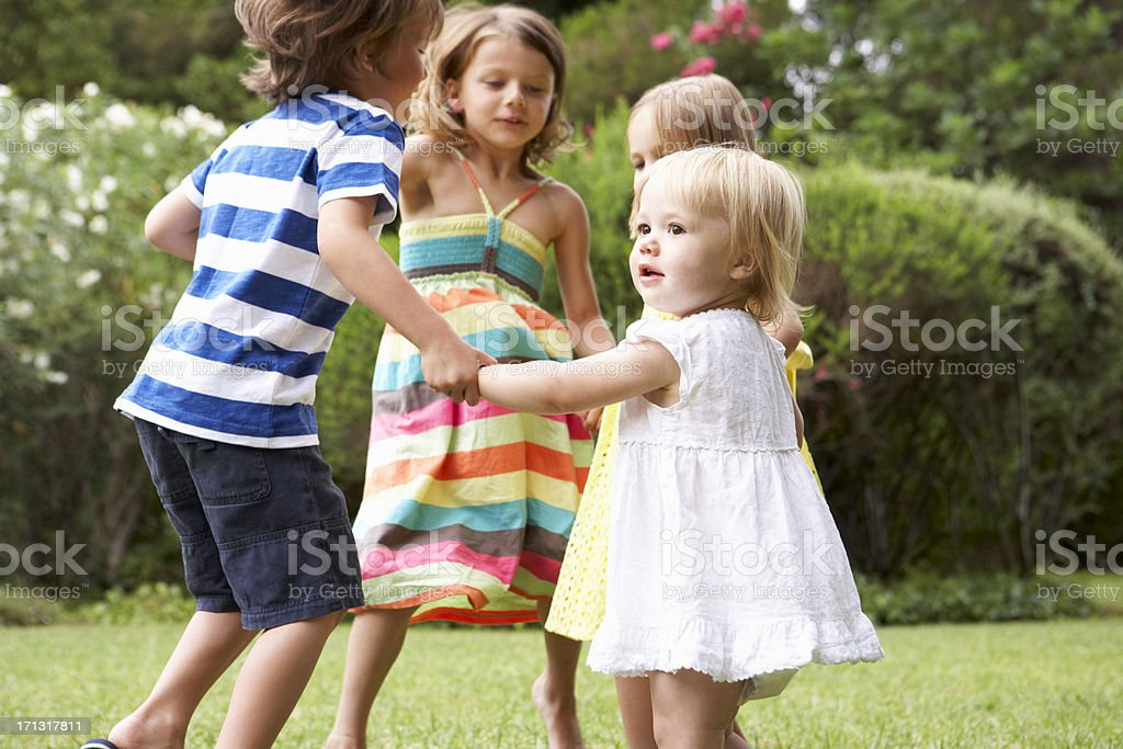 Four children playing in a circle enjoying a summer day stock photo