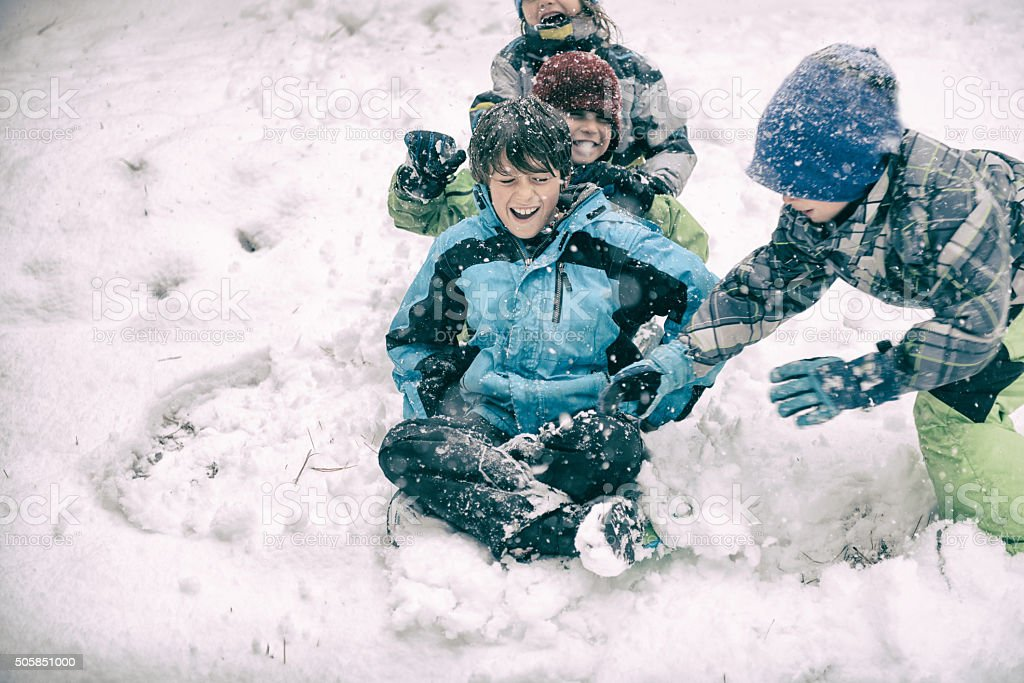 Four children sledding and playing during a big snow storm stock photo
