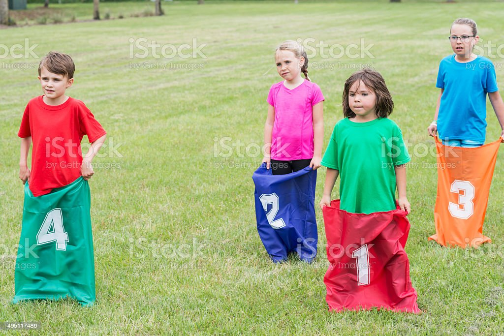 Four children standing, ready for potato sack race stock photo