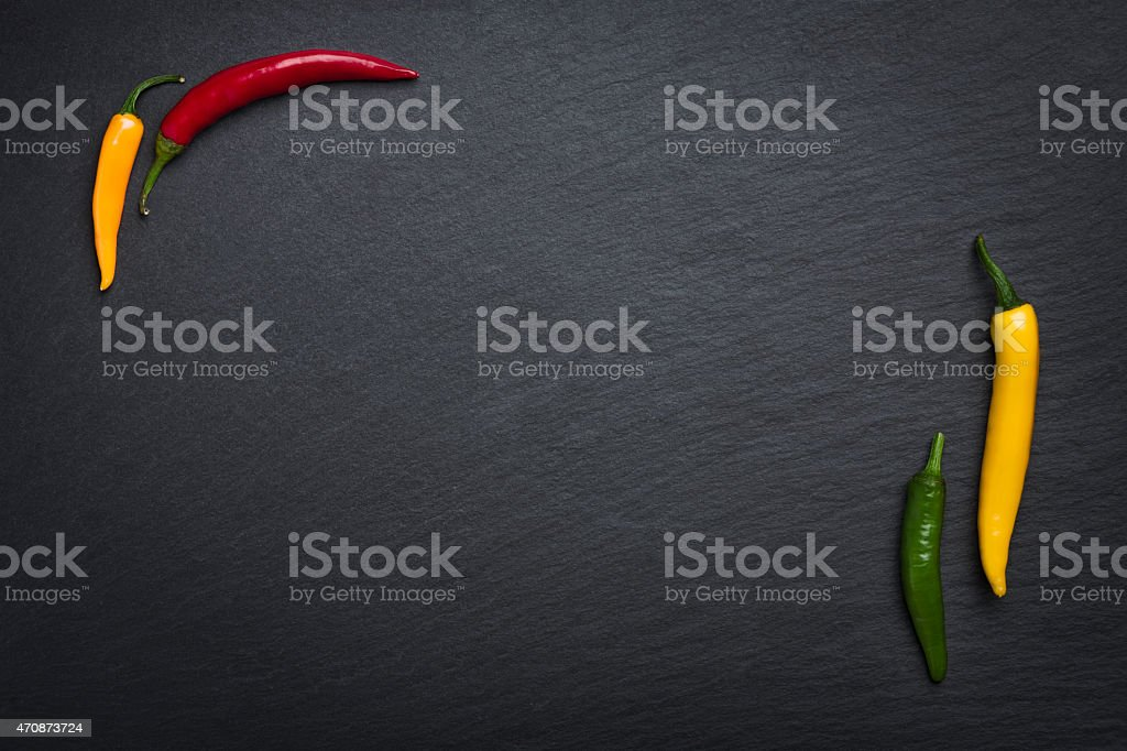 Four chili peppers isolated on slate stone. stock photo