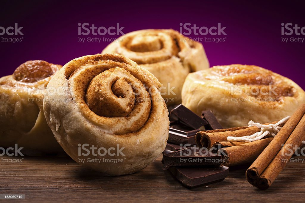 Four cinnamon buns and cinnamon sticks stock photo