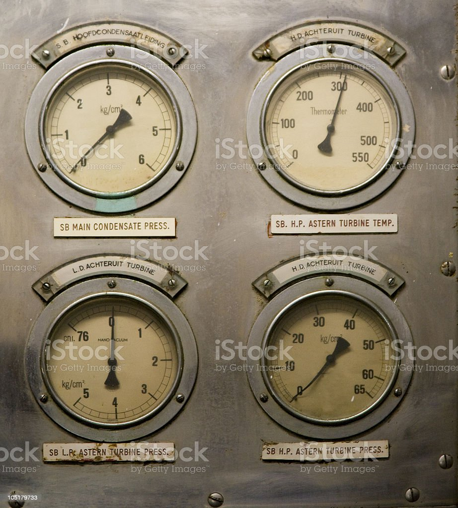 Four circle gauges on a metal panel pointing different ways stock photo