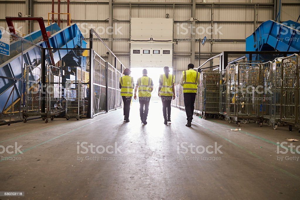 Four colleagues in reflective vests leaving a warehouse stock photo