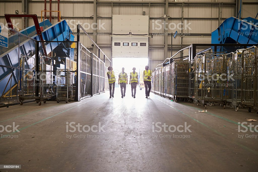 Four colleagues leaving a warehouse approach the exit stock photo