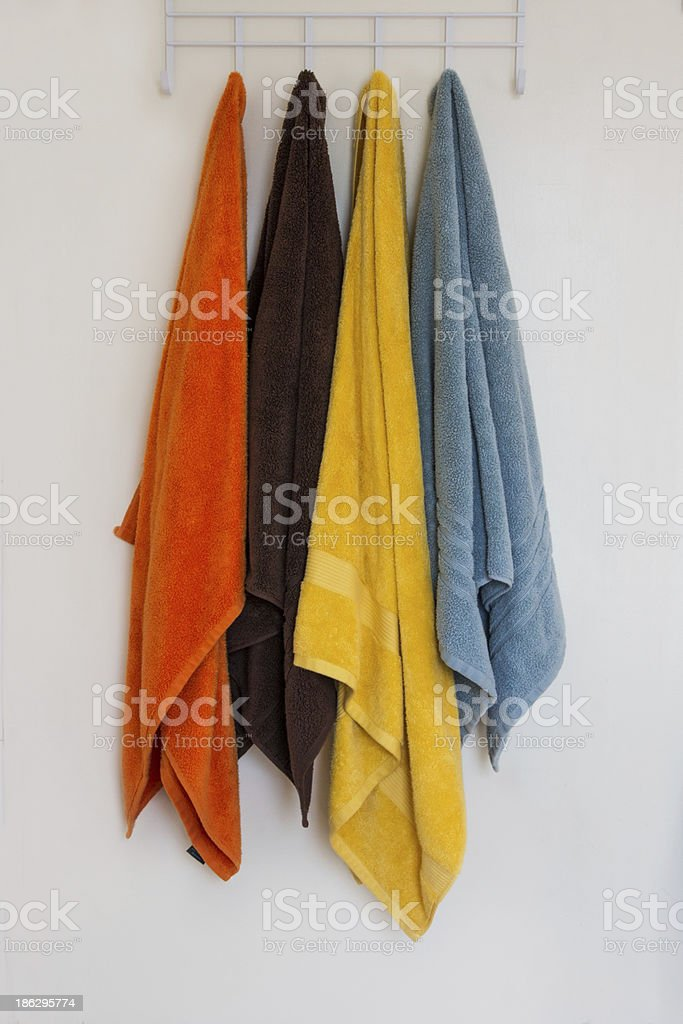 Four Colored Towels Hanging Against White Wall royalty-free stock photo