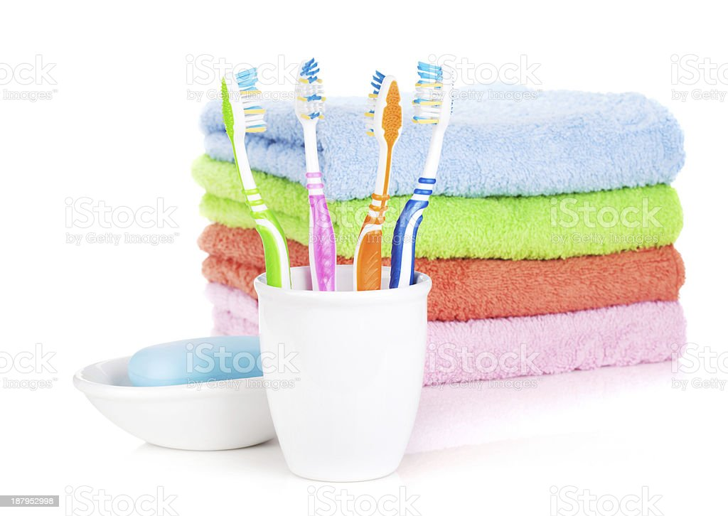 Four colorful toothbrushes, soap and towels royalty-free stock photo