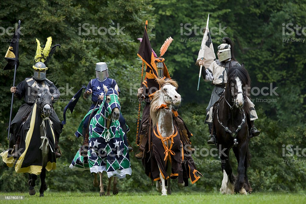 Four colourful knights in suit of armor on horses stock photo