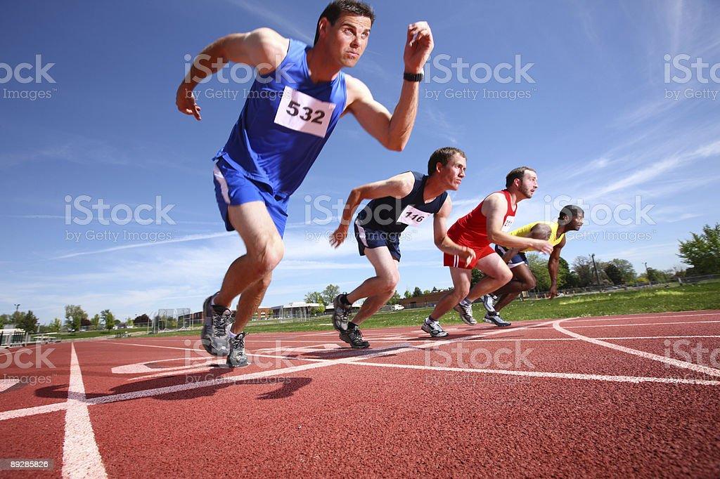 Four men in track event leaving starting line.