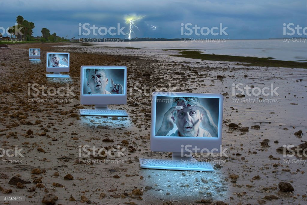 Four computers on stormy beach with emotional man on monitors stock photo