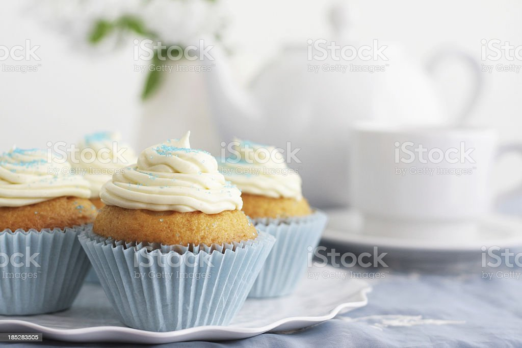Four cupcakes with white icing and tea stock photo